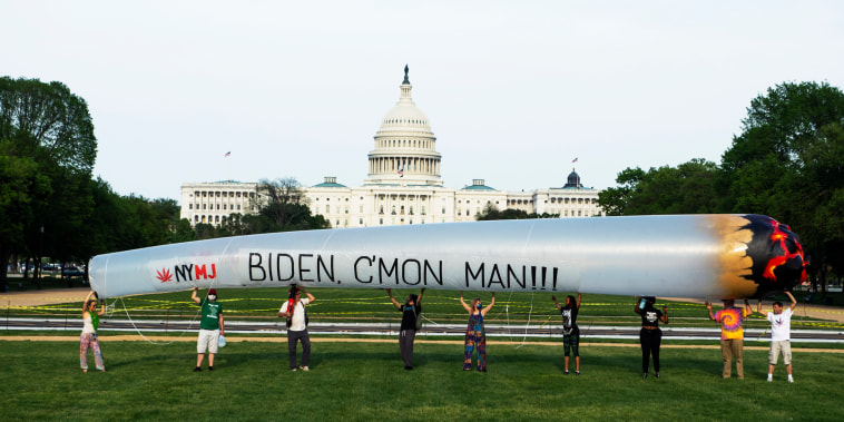 Members of the DC Marijuana Justice community hold a blow-up joint on the National Mall to call on President Joe Biden to take action on legalization and expungement of criminal records on April 28, 2021.