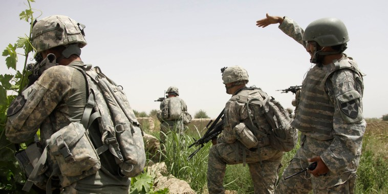 Image: An Afghan interpreter, right,  working on a patrol with of 2nd Platoon, Alpha Company, 2nd Battalion, 1st Infantry Regiment of the 5th Stryker Brigade, calls over some local teenagers  who were seen moving suspiciously in a tree line in Afghanistan