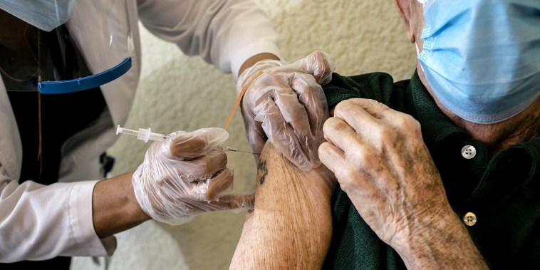 A resident receives a Pfizer-BioNtech Covid-19 vaccine from a healthcare worker at The Palace, an independent living community for seniors, at Coral Gables in Miami, Fla., on Jan. 12, 2021.