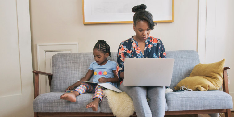 African American mother and daughter relaxing in living room