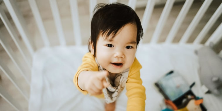 Adorable baby girl standing in her crib and pointing away with fingers