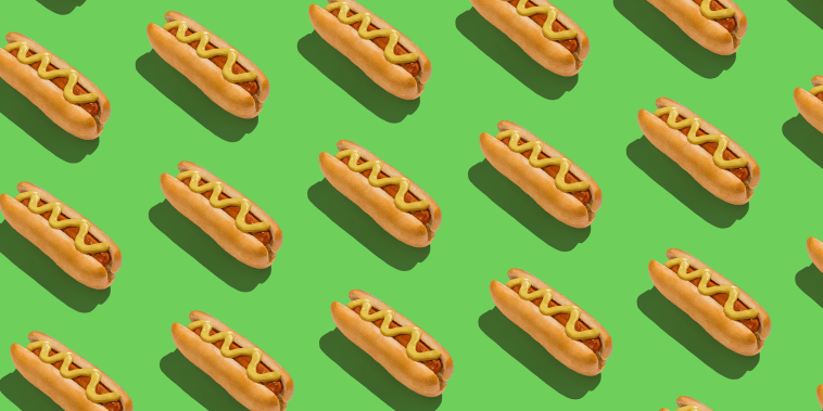 Lots of classic hotdogs with mustard sause over green background, creative pattern
