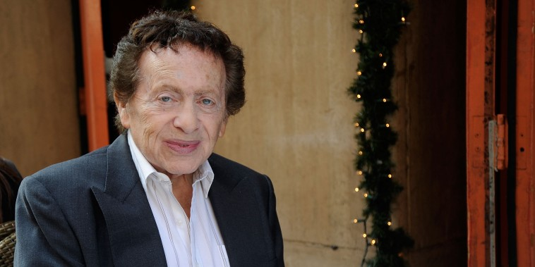 Jackie Mason sits in a suit at a Manhattan restaurant holding a credit card in front of Christmas decor
