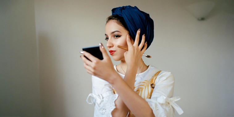 Portrait of young muslim woman applying make up