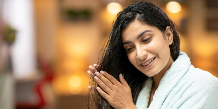 Portrait of a young woman rubbing wet slick hair