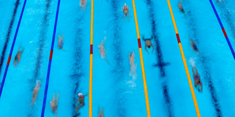 Swimmers warm up before competition at the 2020 Summer Olympics, Sunday, July 25, 2021, in Tokyo.