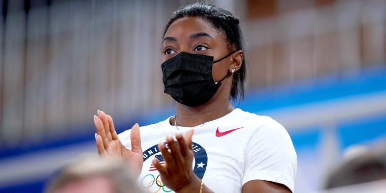 Simone Biles watches from the stands.