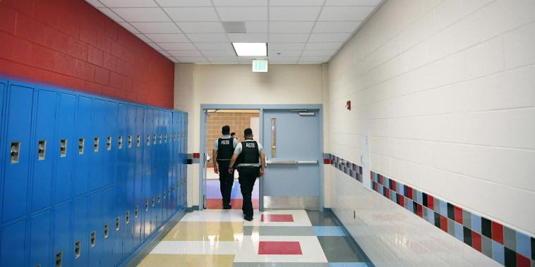 Image: Alexandria Police Department school resource officers walk through a hallway at T.C. Williams High School on June 9, 2021 in Alexandria, Va.
