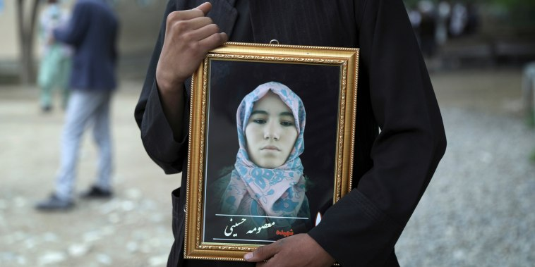 A young man holds a photograph of his sister, who was among those killed in the bombing of a girls school in Kabul, Afghanistan on May 16, 2021.