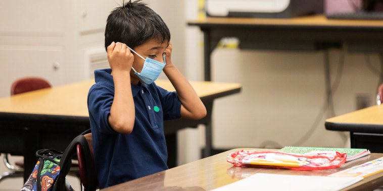 A student puts on his face mask at Garfield Elementary School in Oakland, Calif., on March 30, 2021.