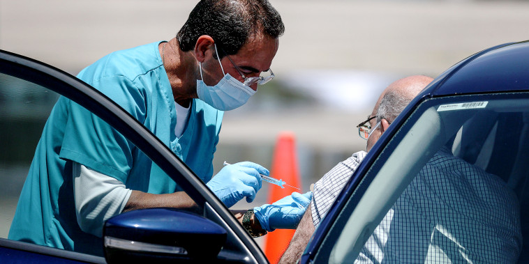 A healthcare worker administers a vaccine at a drive-thru site setup by Miami-Dade and Nomi Health in Tropical Park on July 26, 2021 in Miami.