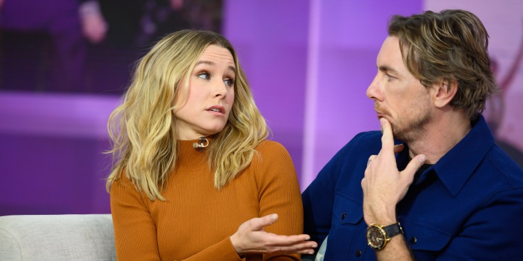 Kristen Bell gestures at her husband Dax Shepard while sitting on a TV set in front of a purple background