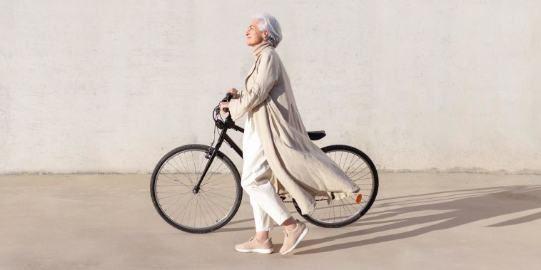 Mature woman walking with bicycle on footpath during sunny day