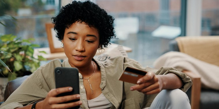 Shot of a young woman holding her credit card while using her cellphone at home