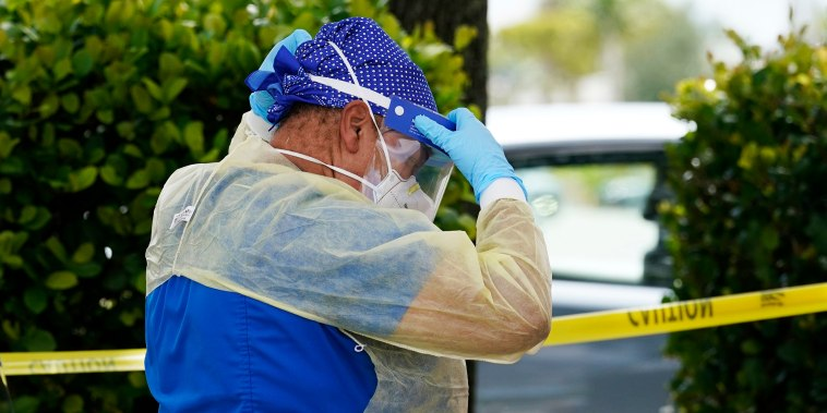Image: A health care worker with Nomi Health puts on a protective face shield while working at a Miami-Dade County Covid-19 testing site on July 26, 2021, in Hialeah, Fla.