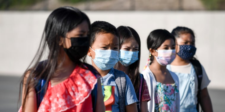 Masked students wait to be taken to their classrooms at Enrique S. Camarena Elementary School on July 21, 2021, in Chula Vista, Calif.