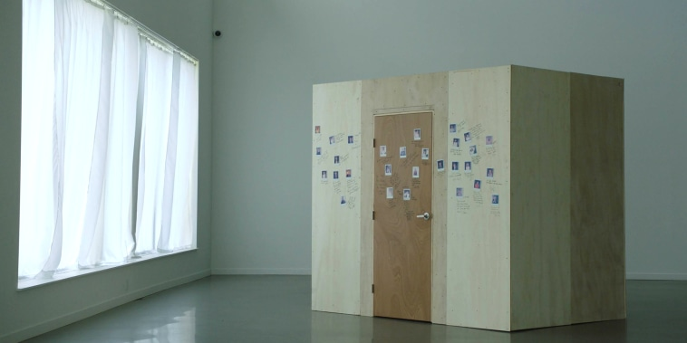 Image: A wooden box with photos on it in a room with a window.