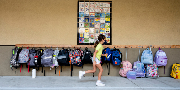 a young girl in yellow t-shirt and white shorts runs in front of a wall of hanging backpacks