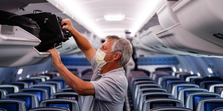 Image: A passenger wears personal protective equipment on a Delta Airlines flight after landing at Minneapolis-Saint Paul International Airport