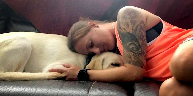 Becca Stephens comforting her service dog Bobbi on the couch in Clearwater, FL.