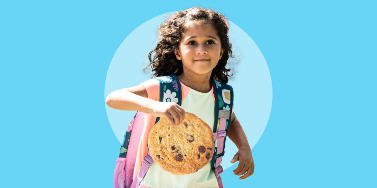 Young girl running outside wearing a backpack with a cookie on her hand