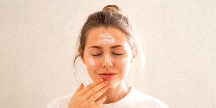 Woman applying face cream in a bathroom