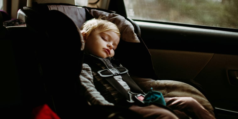 toddler asleep in carseat on road trip