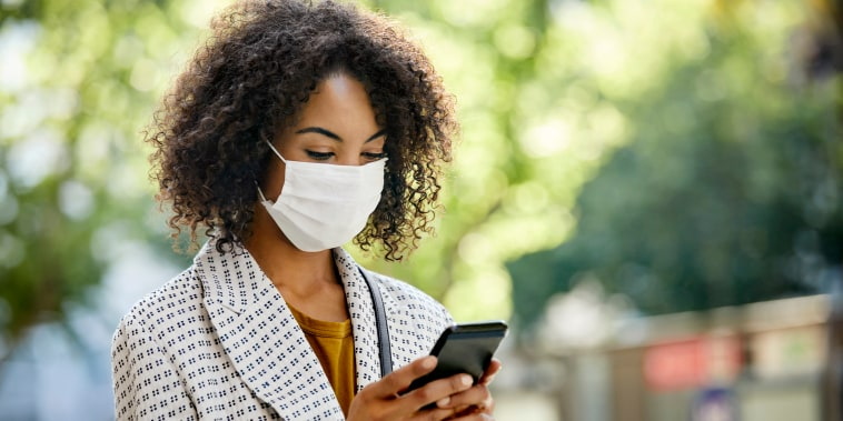 Businesswoman using smart phone during COVID-19 pandemic in city, She is Wearing Protective Face Mask