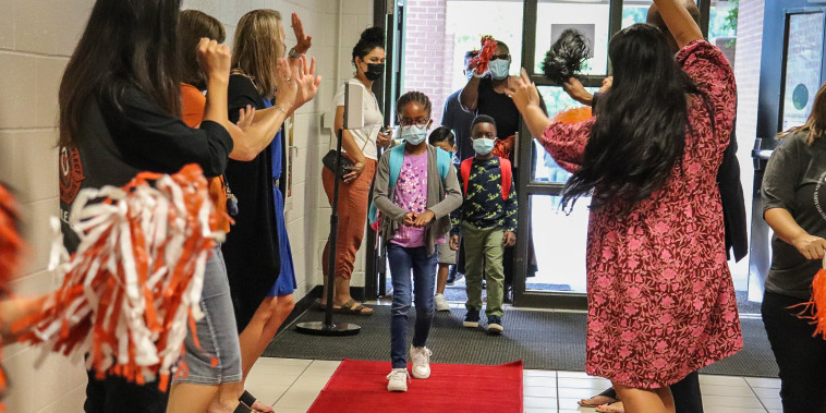 Students walk down a red carpet laid out for them on their first day of school Aug. 4 at Sycamore Elementary School in Sugar Hill, Ga. Across the country, schools are trying to figure out how to best help remote learners re-acclimate to physical classrooms.