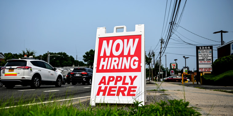 A hiring sign stands along the road in Selden, N.Y., on July 20, 2021.