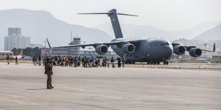 Evacuees load on to a U.S. Air Force Boeing C-17 Globemaster III during an evacuation at Hamid Karzai International Airport, Kabul, Afghanistan, Aug. 21., 2021.