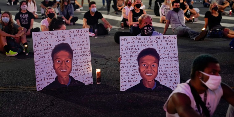 Image: People hold posters showing images depicting Elijah McClain during a candlelight vigil for McClain outside the Laugh Factory in Los Angeles on Aug. 24, 2020.