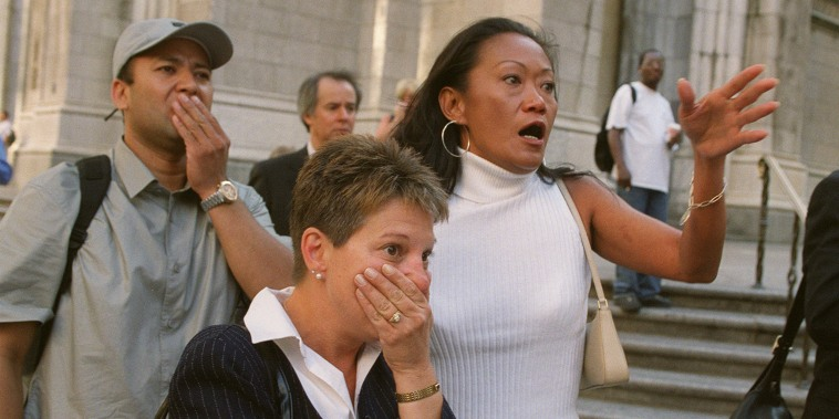 People in front of New York's St. Patrick's Cathedral react with horror as they look down Fifth Ave towards the World Trade Center towers after planes crashed into their upper floors.