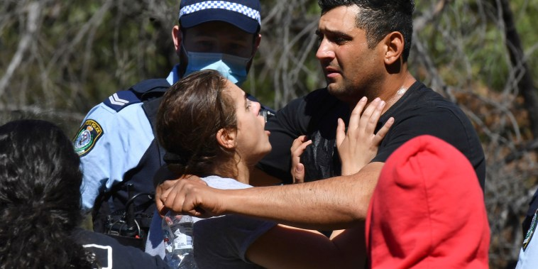 Anthony Elfalak, right, and his wife, Kelly, embrace after hearing their son AJ is found alive on the family property near Putty, north west of Sydney, Australia, Monday, Sept. 6, 2021. Three-year-old AJ was found sitting in a creek and cupping water in his hands to drink three days after he was lost in rugged Australian woodland.