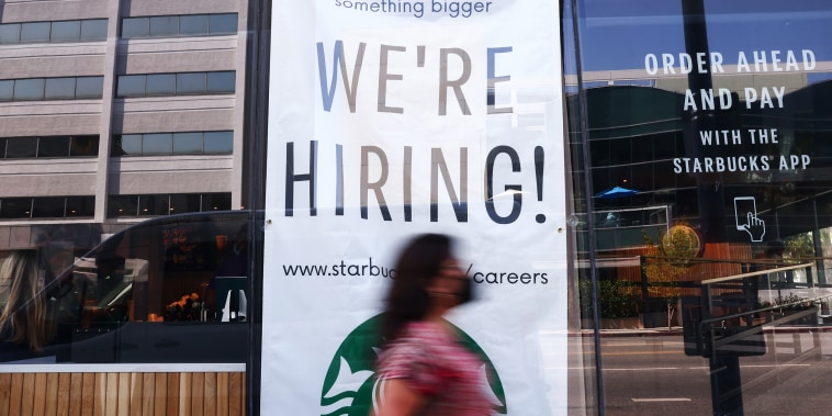 """A """"We're Hiring!"""" sign is posted at a Starbucks on Aug. 6, 2021 in Los Angeles."""