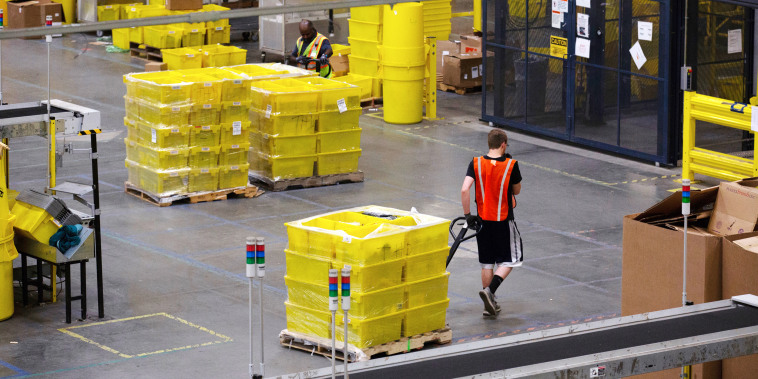 An employee pulls a pallet jack carrying plastic crates containing online orders at the Amazon fulfillment center in Robbinsville, N.J., on June 7, 2018.