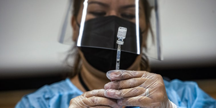 A healthcare worker prepares a dose of the Pfizer-BioNTech Covid-19 vaccine at a mobile vaccination clinic at a high school in Los Angeles on Aug. 30, 2021.