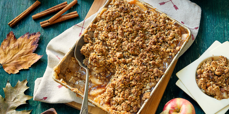 Autumn themed overhead view of baked apple crisp with oat crumble topping. With maple leaves & acorns