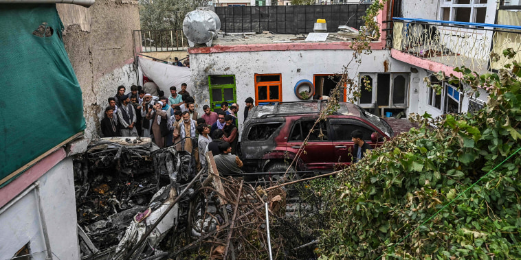 Image: Afghan residents and family members of the victims gather next to a damaged vehicle inside a house, day after a U.S. drone airstrike in Kabul on Aug. 30, 2021.