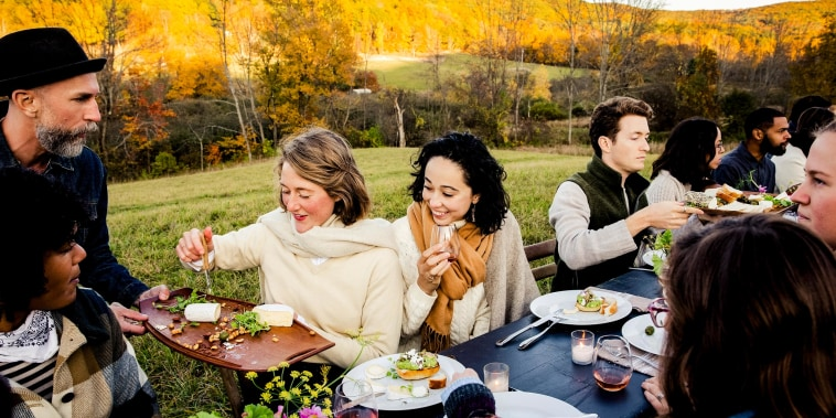 Man serving food to guests at dinner party in field, during the fall