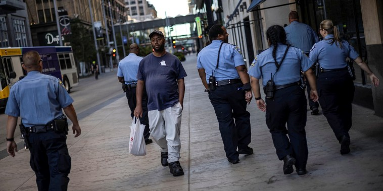 A man walks by a group of police officers in downtown Minneapolis on Sept. 8, 2021.