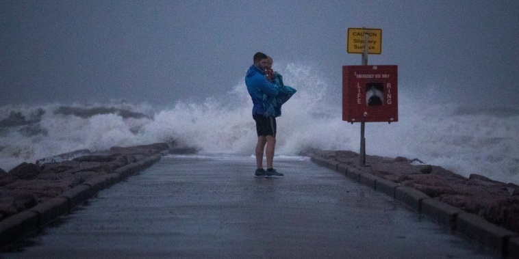 A Texas resident holds his son as he stands near breaking waves on a pier ahead of the arrival of Tropical Storm Nicholas in Galveston, Texas, on Sept. 13, 2021.