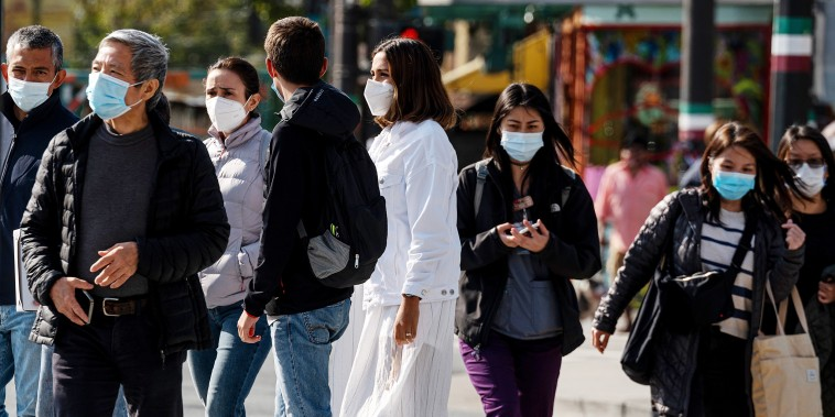 Image: Pedestrians wear protective masks on a street as vaccine requirements are in effect in San Francisco on Aug. 24, 2021.