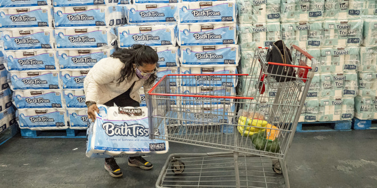 A customer wearing a protective mask puts a bundle of bath tissue onto a shopping cart inside a Costco.