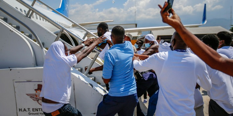 Image: Deported Haitians try to board plane back to USA