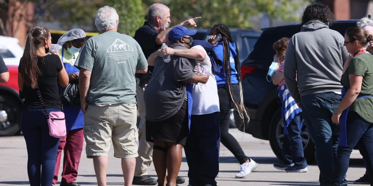 Image: People hug outside the Kroger in Collierville, Tenn., at the scene of a shooting on Sept. 23, 2021.