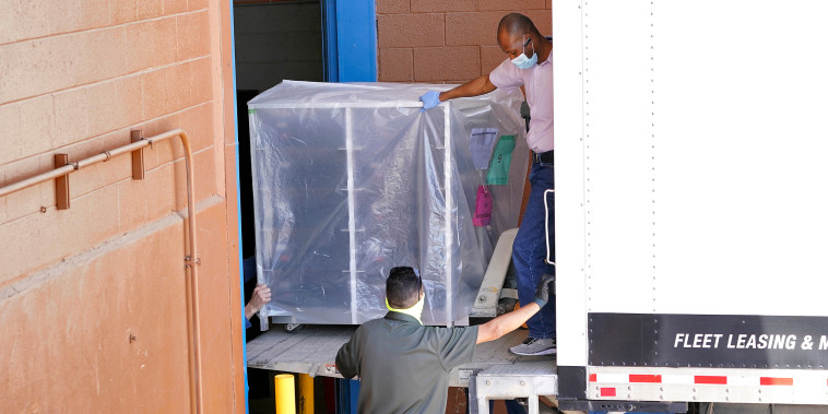 Image: Officials unload election equipment into the Veterans Memorial Coliseum at the state fairgrounds in Phoenix, on April 21, 2021