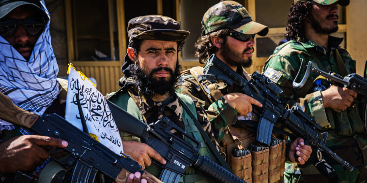 Taliban fighters line up to show off their weapons as they control access to the Abbey Gate and make Afghans with travel documents wait in Kabul, Afghanistan, on Aug. 25, 2021.
