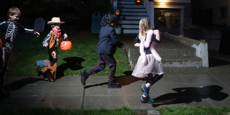 Young children trick or treating on Halloween