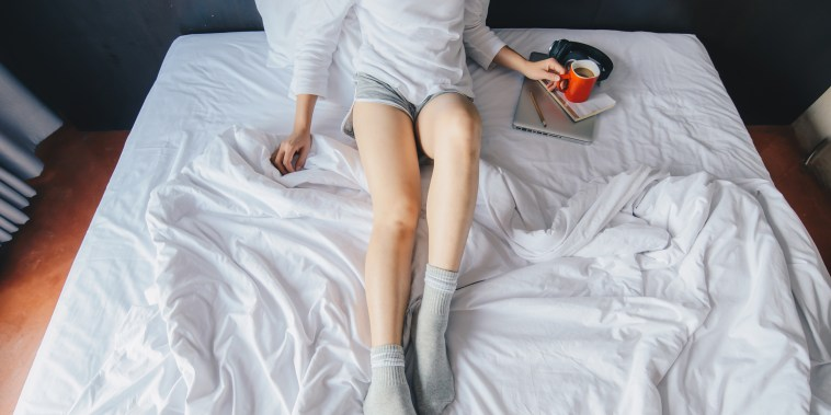 Woman laying in bed with cozy socks and a mug on her laptop